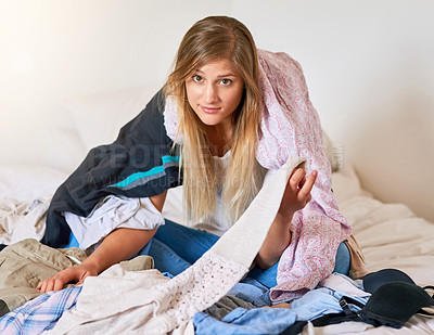 Buy stock photo Portrait of a young woman sitting in a pile of laundry at home