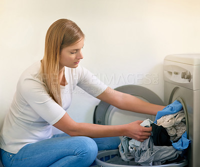 Buy stock photo Cropped shot of a young woman doing laundry at home