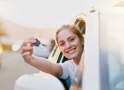 Buy stock photo Portrait of a young woman holding the keys to her car while sitting inside it