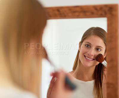 Buy stock photo Shot of a young woman applying blusher in front of a mirror at home