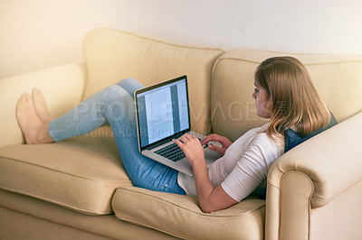 Buy stock photo Shot of a young woman using her laptop while sitting on the couch at home