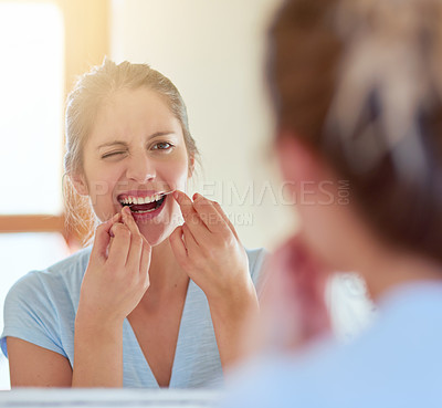 Buy stock photo Cropped shot of a young woman flossing her teeth in a mirror