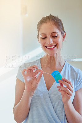 Buy stock photo Cropped shot of a young woman flossing her teeth in a bathroom