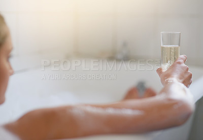 Buy stock photo Cropped shot of a young woman relaxing in the bathtub with a glass of wine