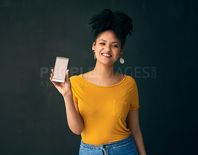 Buy stock photo Shot of a young woman holding a cellphone while posing against a grey background