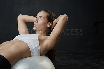 Buy stock photo Studio shot of an attractive young woman working out against a dark background