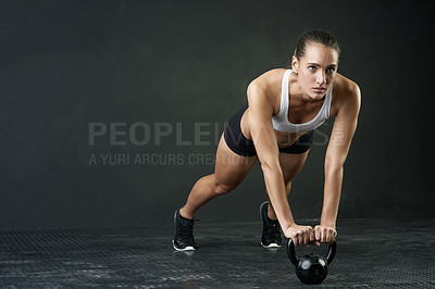 Buy stock photo Studio shot of an attractive young woman working out with a kettle bell against a dark background