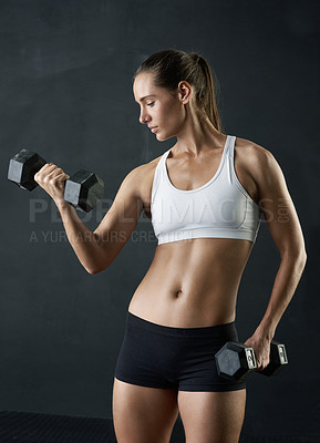 Buy stock photo Studio shot of an attractive young woman working out with dumbbells against a dark background