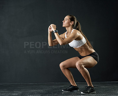 Buy stock photo Studio shot of an attractive young woman doing squats against a dark background
