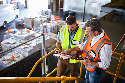 Buy stock photo Shot of two warehouse workers standing on stairs using a digital tablet and looking at paperwork