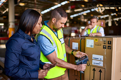 Buy stock photo Shot of workers scanning boxes with a barcode reader while working inside a large warehouse