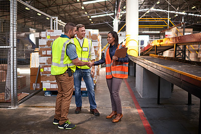 Buy stock photo Shot of two workers shaking hands together while standing in a large warehouse