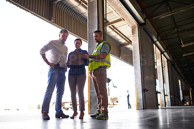 Buy stock photo Shot of three workers standing inside the entrance to a large warehouse