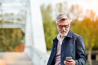 Buy stock photo Shot of a mature man using a cellphone while leaning on a railing in the city