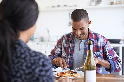 Buy stock photo Shot of a young couple talking together over dinner in their kitchen