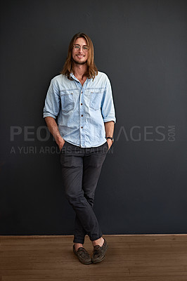 Buy stock photo Studio portrait of a smiling young man standing with his arms crossed against a gray background