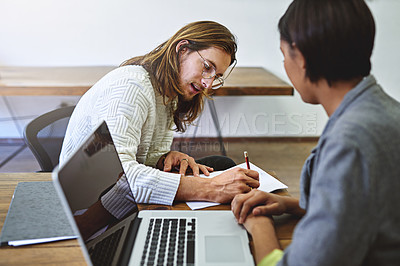 Buy stock photo Shot of two smiling colleagues working together in an office