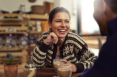 Buy stock photo Shot of a young couple enjoying their date at a local coffee shop