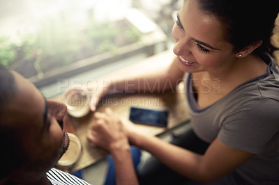Buy stock photo High angle shot of a young couple enjoying their date at a local coffee shop