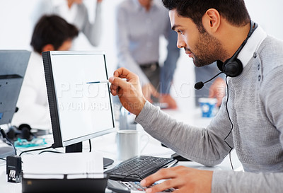 Buy stock photo Business man using computer with colleagues discussing in background