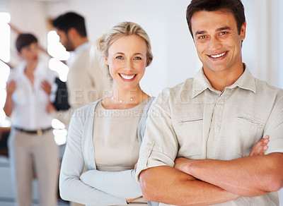 Buy stock photo Confident business man and woman smiling with colleagues discussing in background