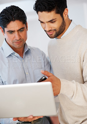 Buy stock photo Two serious business men working together on laptop