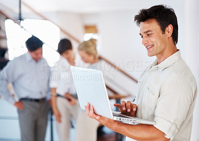 Buy stock photo Happy business man using laptop and smiling with colleagues in background