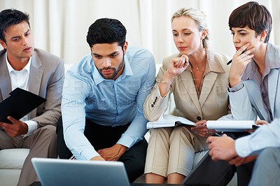 Buy stock photo Business colleagues discussing with each other using laptop