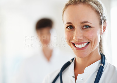 Buy stock photo Closeup of beautiful female doctor smiling with colleague in background