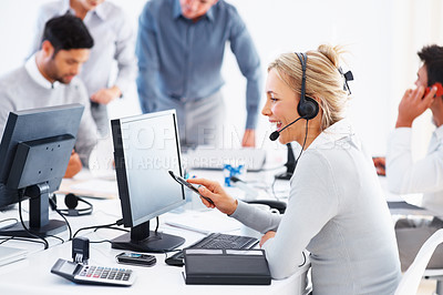 Buy stock photo Beautiful call center representative talking on headset and working on computer