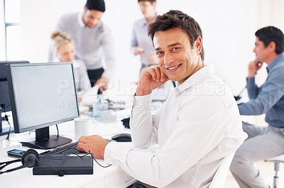Buy stock photo Smiling male executive using computer with colleagues discussing in background