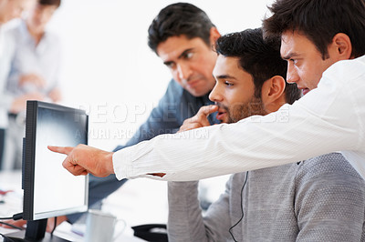 Buy stock photo Business man points something out to his colleagues on computer during meeting
