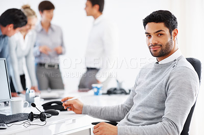 Buy stock photo Confident business man sitting in front of computer with colleagues discussing in background