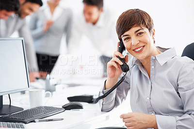 Buy stock photo Happy business woman on telephonic conversation with colleagues in background