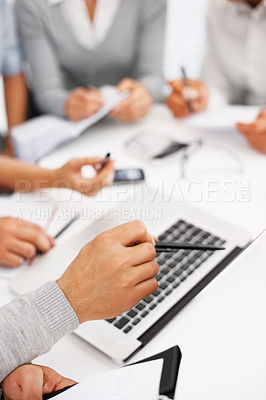 Buy stock photo Cropped image of leader pointing at laptop with colleagues in background