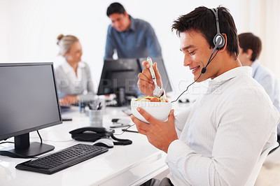 Buy stock photo Happy business man eating at desk during break with colleagues in background