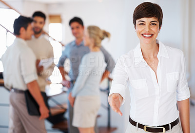 Buy stock photo Short haired business woman offering you handshake with colleagues discussing in background