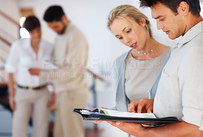 Buy stock photo Business man and woman reviewing documents with colleagues discussing in background