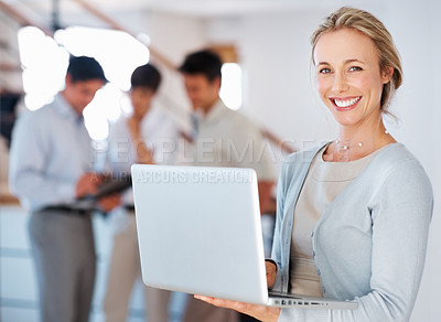 Buy stock photo Portrait of business woman using laptop and giving you cute smile with colleagues in background