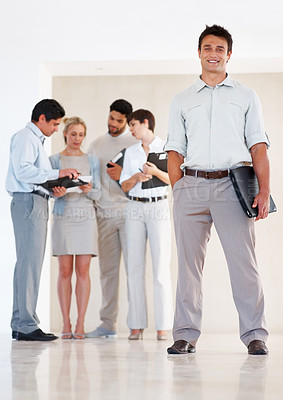 Buy stock photo Full length of confident business man standing with colleagues discussing in background