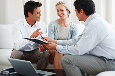 Buy stock photo Consultant giving new investment plans to smiling business couple for signing
