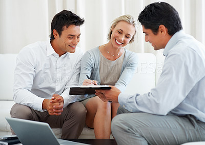 Buy stock photo Couple during consultancy meeting with woman signing contract