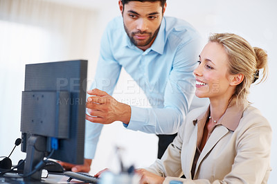 Buy stock photo Smiling business woman working on computer with male executive pointing at the screen