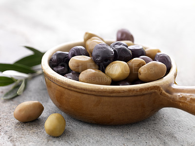 Buy stock photo Closeup of dried black and green olives in a ceramic bowl on floor