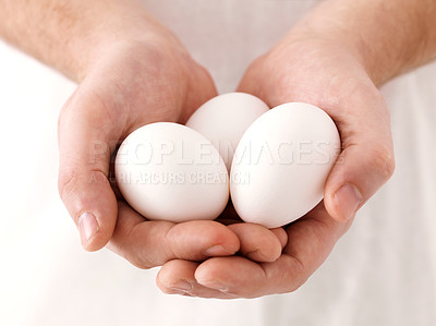 Buy stock photo Closeup portrait of three white eggs in human hand