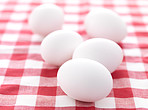 Farm fresh white eggs on picnic tablecloth