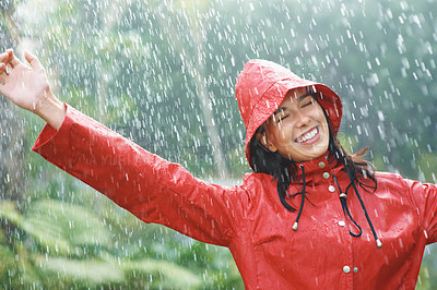 Buy stock photo Happy woman in red raincoat smiling as she plays in rain