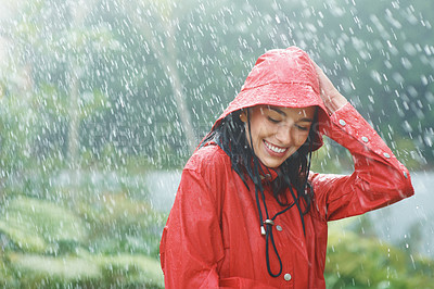 Buy stock photo Happy young woman holding her hat while outside in a fresh rain shower - copyspace