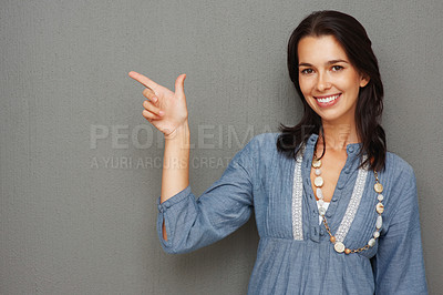 Buy stock photo Pretty woman casually dressed and pointing at copyspace