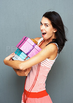Buy stock photo Beautiful woman with a surprised look hugging a pile of presents, against a grey background - copyspace